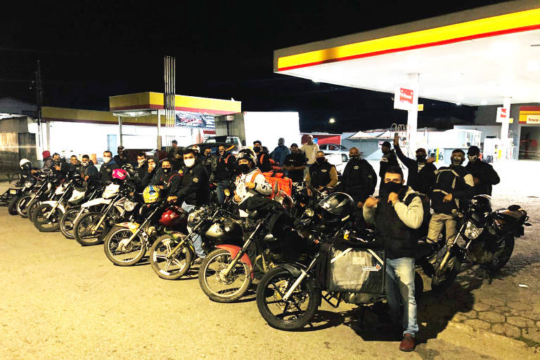 Dezenas de motos estão estacionadas em frente a um posto de combustível, à noite