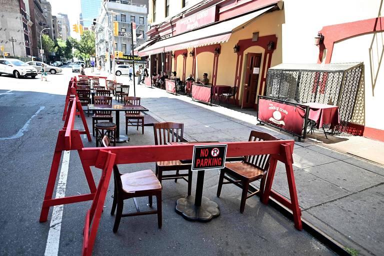 """Mesas de restaurante colocadas em rua de Nova York, que permitiu consumo de alimentos em áreas externas a partir de 22 de junho; as mesas estão na faixa que seria para estacionamento, no leito da rua, cercadas por cavaletes de madeira simples, com dizeres """"no parking"""", """"proibido estacionar"""""""