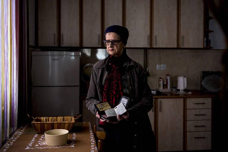 Foto mostra uma mulher, em pé em uma cozinha simples, com olhar cabisbaixo. Ela está bem agasalhada e segura os documentos do marido. A luz é natural, mas indireta