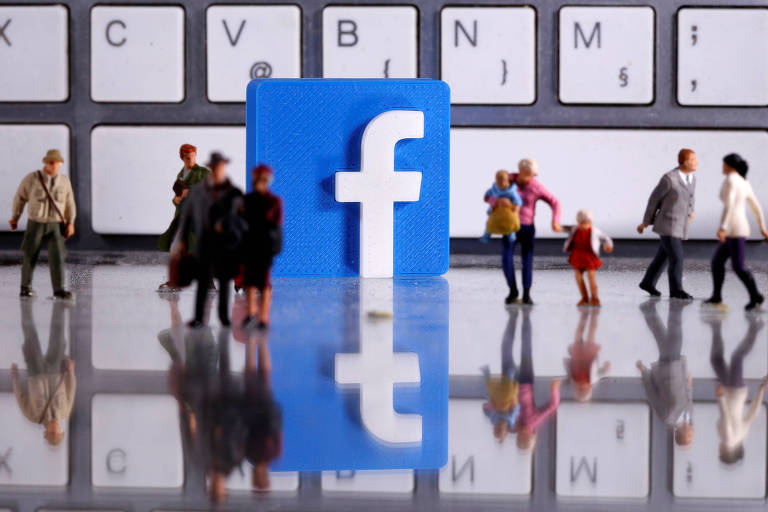 bonecos de seres humanos em miniatura caminham em frente a um logo do facebook colocado em frente a um teclado de computador