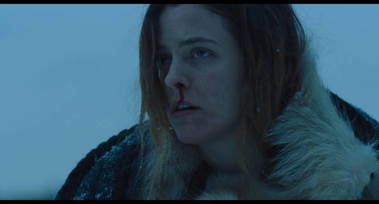 Uma mulher usa um casaco de pele num cenário de neve. Seu nariz está sangrando.