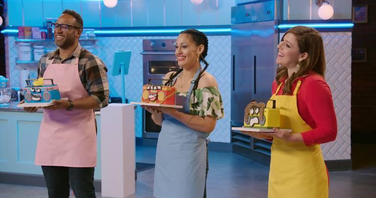 três competidores mostram seus bolos em forma de rádio aos jurados