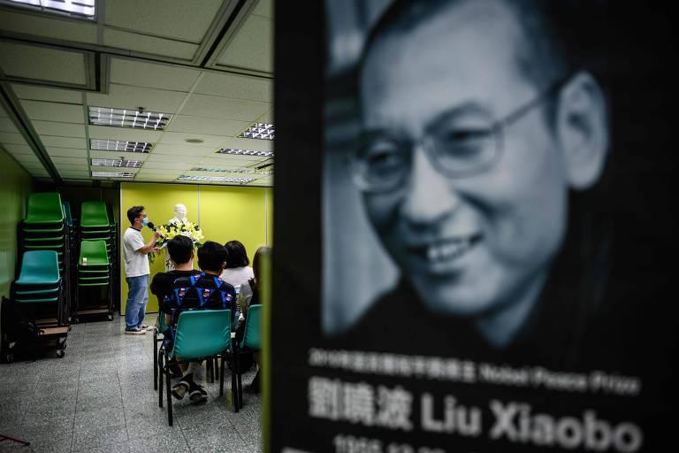 """Ativistas se reúnem para relembrar o terceiro aniversário da morte do dissidente chinês Liu Xiaobo (à dir.), que foi preso em 2009 e acusado de """"incitar subversãodo poder estatal"""""""