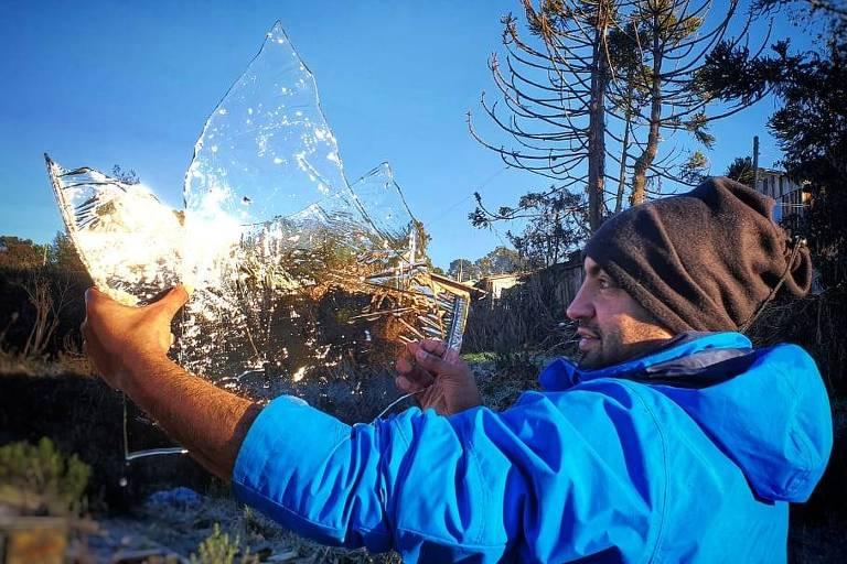 Homem mostra camada de gelo que se formou no Caminhos da Neve, em São Joaquim (SC)