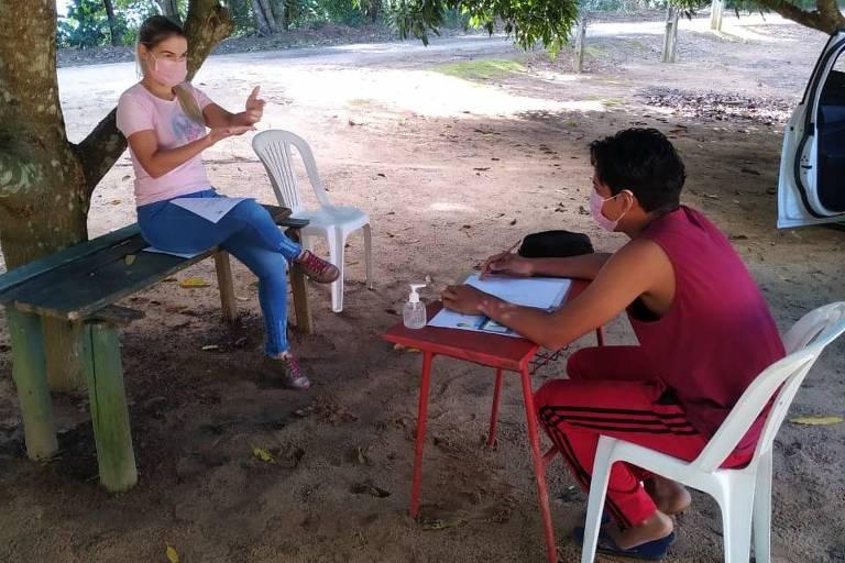 Debaixo de uma árvore, um adolescente está sentado em uma cadeira em frente a uma pequena mesa. à sua frente, uma mulher faz sinais de Libras para se comunicarem.