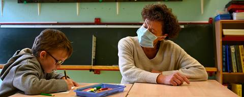 A teacher wearing a protective mask talks with a child in her classroom at Champ l'Eveque public school in Bruz, western France, on May 12, 2020, after France eased lockdown measures taken to curb the spread of the COVID-19 pandemic, caused by the novel coronavirus. (Photo by Damien MEYER / AFP)