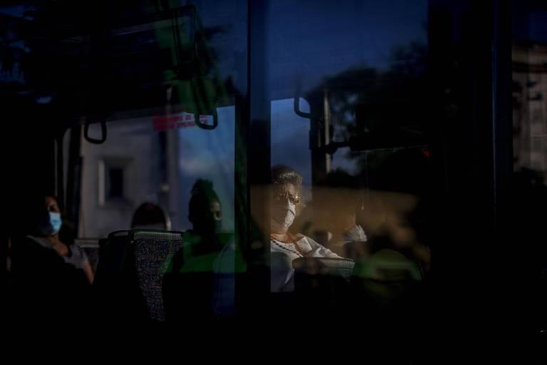 Mulher com máscara em ônibus na periferia de Lisboa, em Portugal