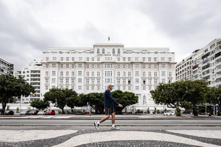 Copacabana Palace é visto ao fundo, com várias árvores na frente. Um senhor de camiseta azul e máscara caminha