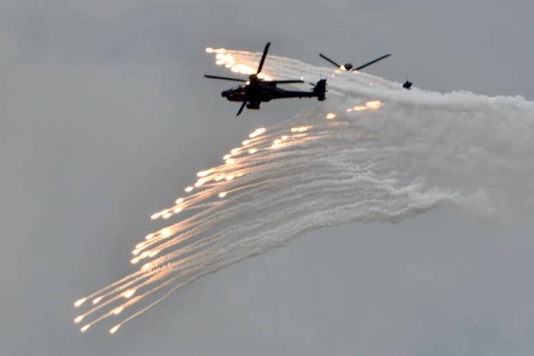 Dois helicópteros são vistos entre rajadas de munição