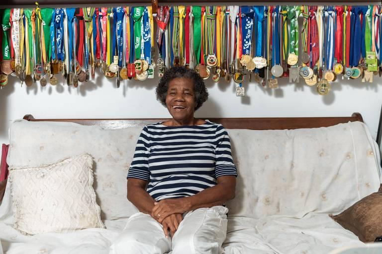 Mulher idosa negra sentada no sofá com diversas medalhas penduradas em estante atrás dela