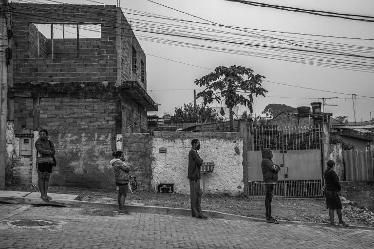 Cinco pessoas em fila na rua, com distanciamento entre elas, na frente de casas na periferia