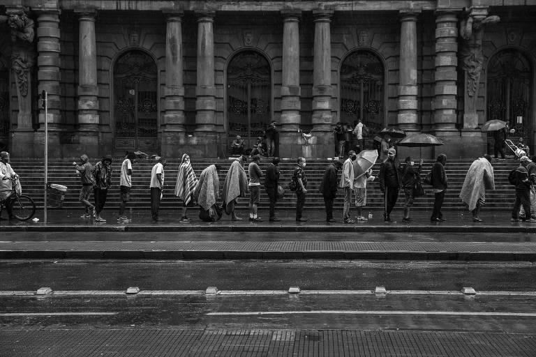 Pessoas em situação de rua aguardam para receber marmita doadas por voluntários, na Praça Ramos de Azevedo, no centro de São Paulo
