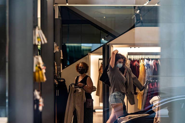 Cliente prova roupa em loja de Nova York; vendas já subiram com reabertura
