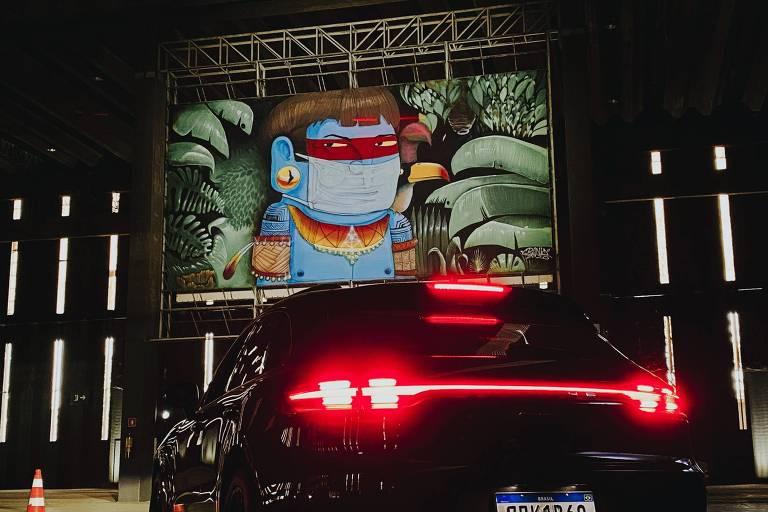 Carro em frente a um mural com uma obra do artista Crânio