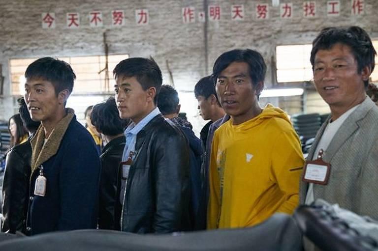 trabalhadores passam por fila de montagem em fábrica