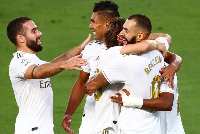 Benzema sorri, abraçado por companheiros