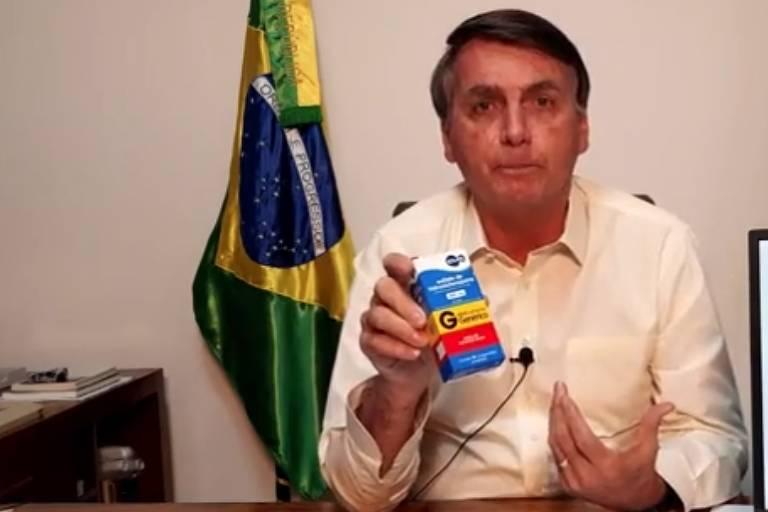 O presidente Jair Bolsonaro segura uma embalagem de medicamento genérico