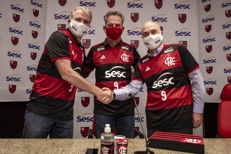 Bernardinho aperta a mão de Queiroz, com Landim ao centro, todos de máscara e camisa do Flamengo