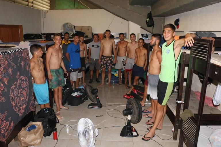 Dez jovens de pé, alguns sem camisa, estão apoiados em beliches e camas dentro de um estádio. Há ventiladores ligados no chão.
