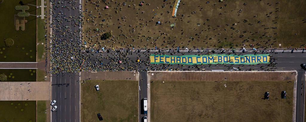 Imagem aérea mostra manifestantes ao redor de faixa com os dizeres