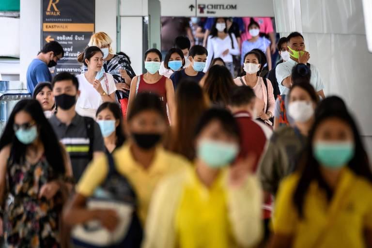 Pessoas caminham em ponte para pedestres usando máscara de proteção facial