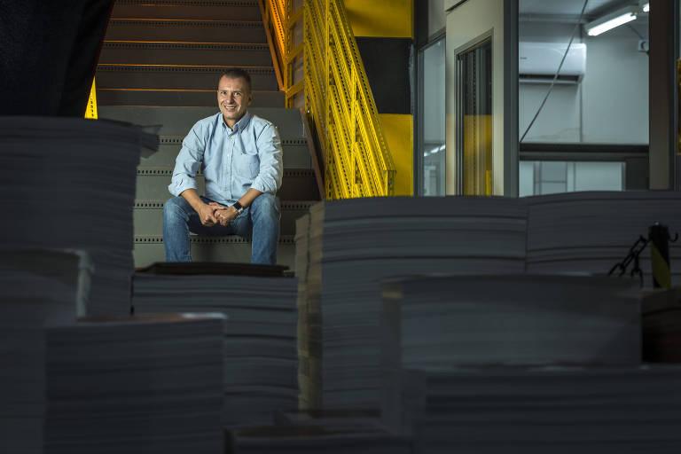 Luiz sentado nos degraus de uma escada com corredor amarelo, com caixas empilhadas à sua frente