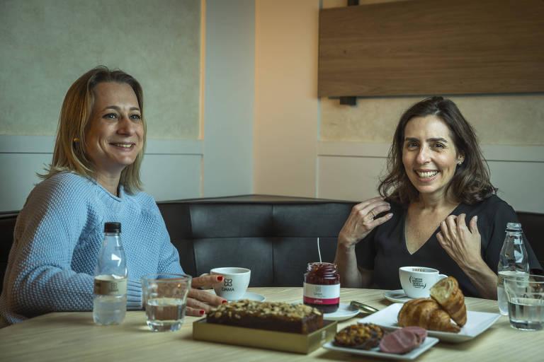 Sorrindo, Daniela e Mariana estão sentadas à mesa, que tem geleia, bolos, doces, xícaras de café e garrafas de água