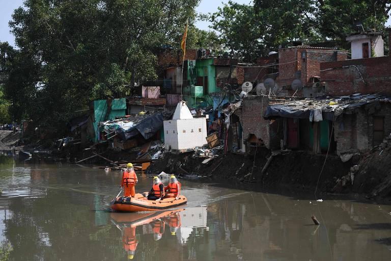 Membros de equipe de resposta a desastres naturais inspecionam área onde casas colapsaram devido a fortes chuvas em Nova Déli
