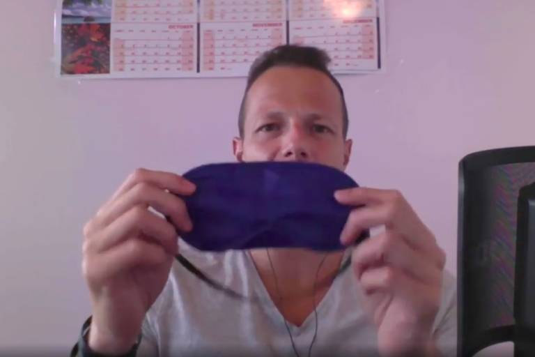 Homem mostra máscara azul ao gravar vídeo em frente a computador