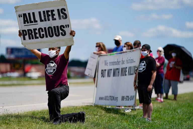 Ativista com cartaz que leva a frase 'toda vida é preciosa' protesta contra execução de condenado à morte no centro de detenção Terre Haute, em Indiana