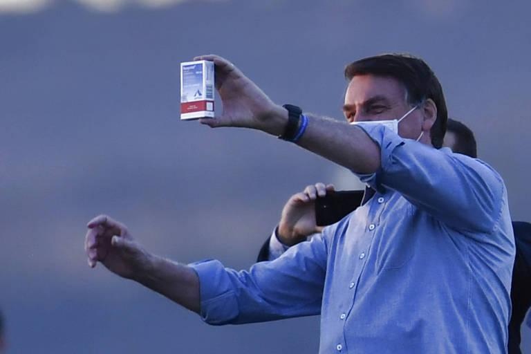 Bolsonaro mostra caixa de hidroxicloroquina a apoiadores, que aplaudem, na frente do Palácio da Alvorada