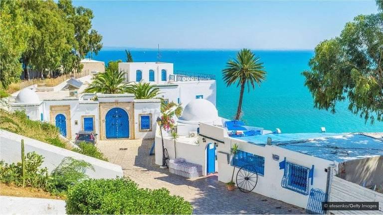 Construções pintadas de branco e azul com mar ao fundo