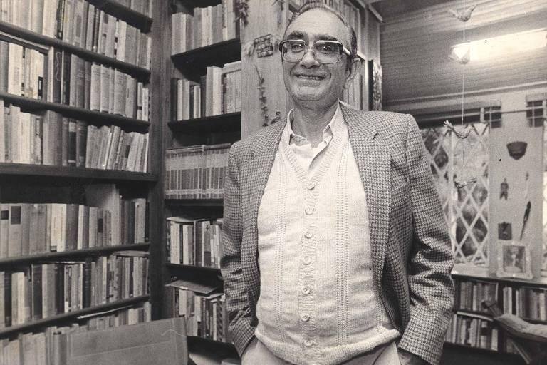 Florestan Fernandes sorrido, com as mãos no bolso. Ao fundo, estante de livros