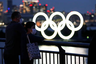 The giant Olympic rings are seen in front of the visitors wearing protective face masks, in Tokyo