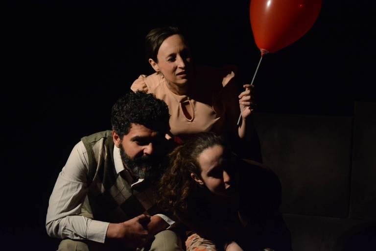família com balão vermelho