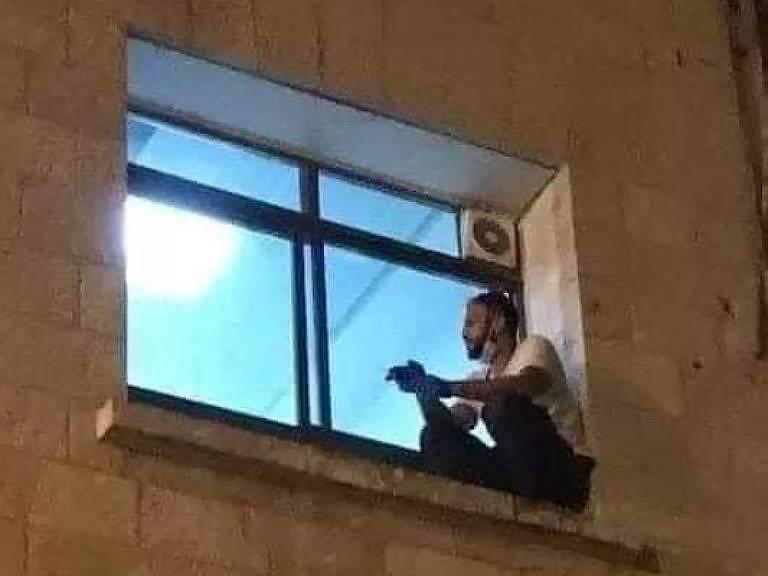 Homem sentado em janela de hospital
