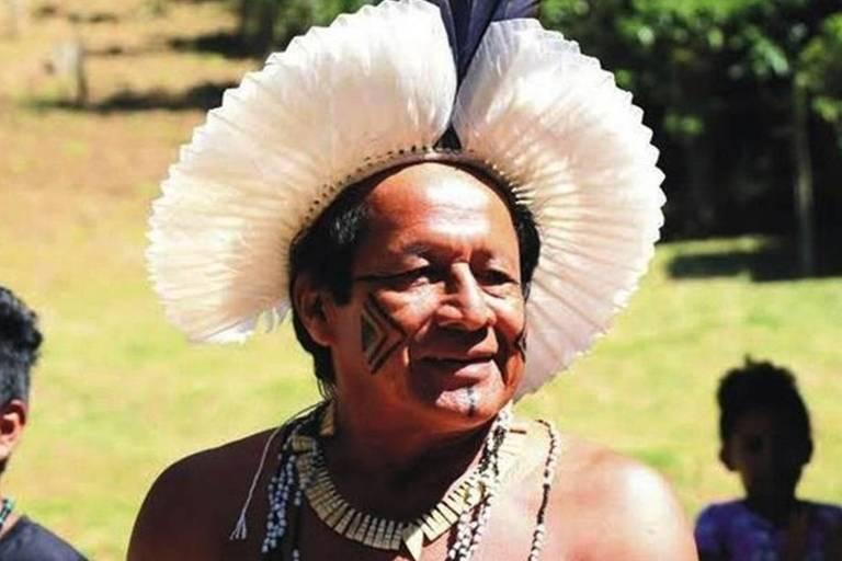 Um índio usa um cocar de penas brancas e correntes no pescoço, com crianças indígenas ao fundo.