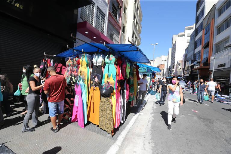 Comércio popular na região da 25 de Março, no centro de São Paulo; várias pessoas caminham de máscaras ao redor de estandes