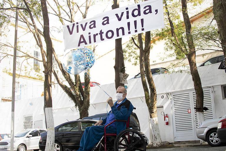 Airton dos Santos posa embaixo da faixa em sua homenagem, na saída do hospital