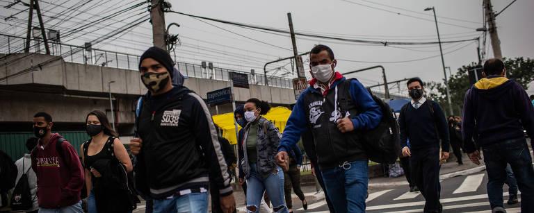 Pessoas com máscara atravessam uma faixa de pedestres