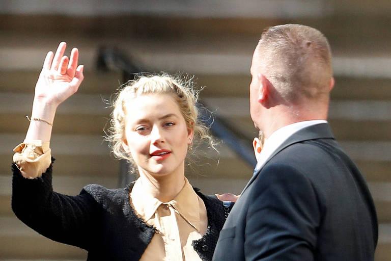A atriz Amber Heard acena ao deixar Suprema Corte de Londres