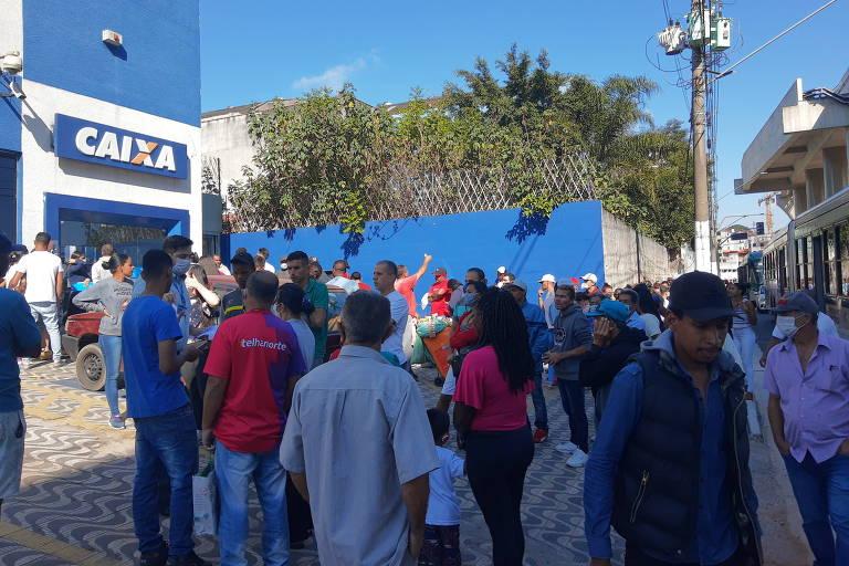 Pessoas esperam em fila para sacar auxílio emergencial em uma agência da Caixa Econômica Federal em São Paulo