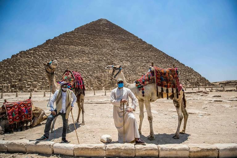 Homens com roupas árabes e camelos em frente a pirâmide