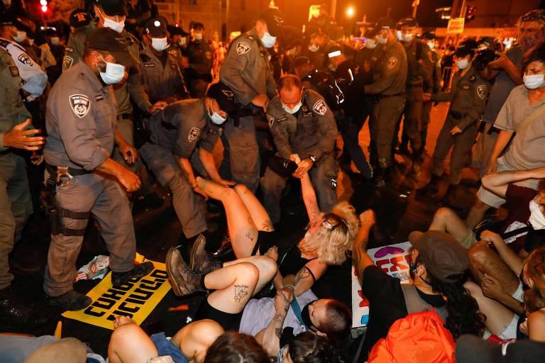 Policiais retiram à força manifestantes que bloqueavam rua durante protesto contra o premiê israelense, Binyamin Netanyahu, na madrugada desta quarta (22)