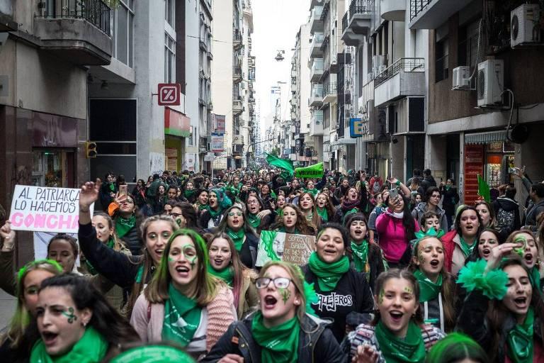 Multidão de mulheres com lenços verdes enrolados no pescoço