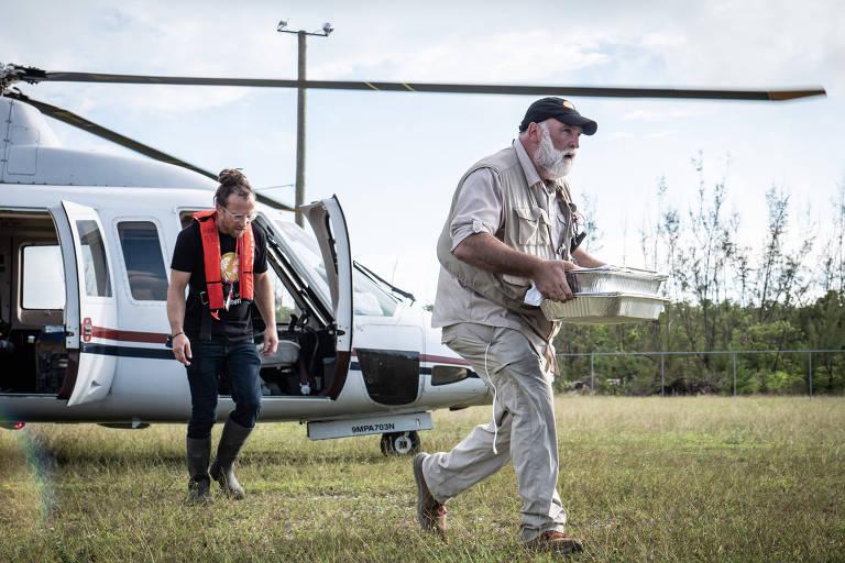 senhor de boné saindo de helicoptero e outro homem atrás