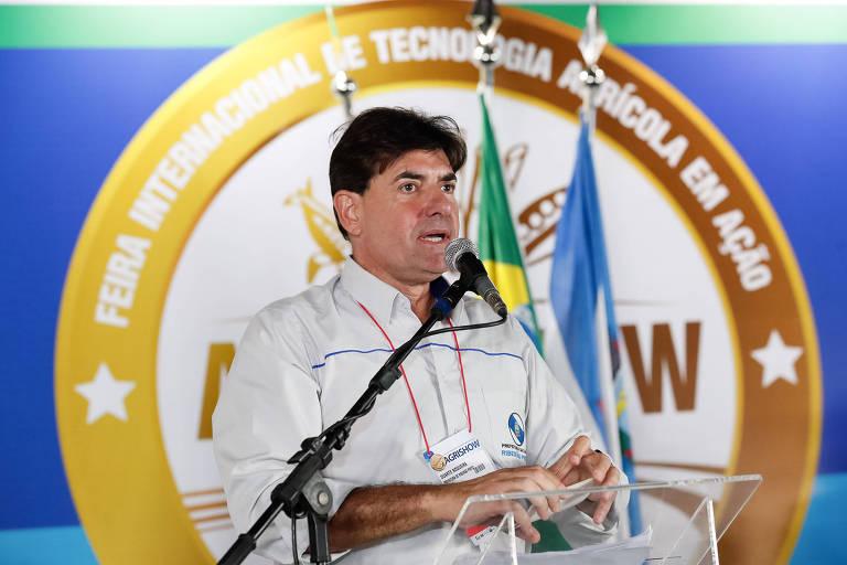 Prefeito de Ribeirão Preto fala ao microfone e, ao fundo, há bandeiras da cidade e do país