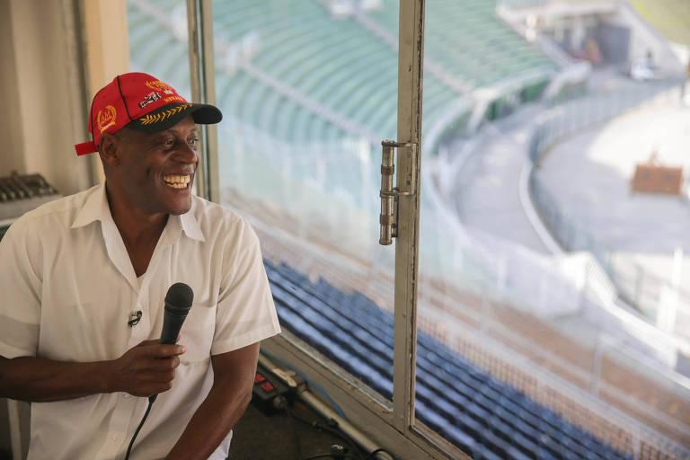 Edson Sorriso com camisa branca, boné vermelho e o microfone na mão em cabine de locução do estádio