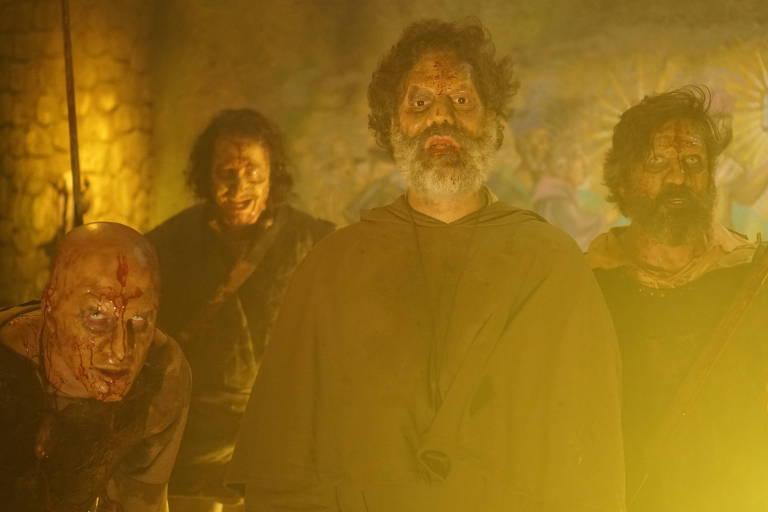 Quatro homens com aspecto de zumbis estão de frente para a foto. Todos eles têm manchas de sangue no rosto