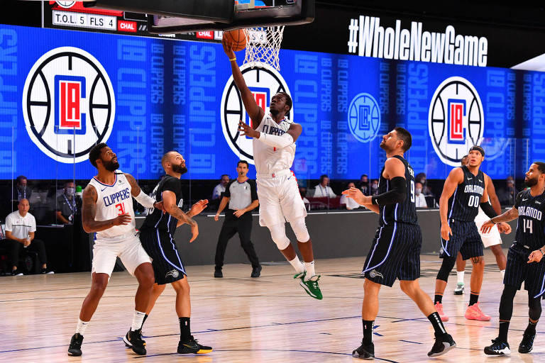 Reggie Jackson, jogador dos Clippers, de branco, faz uma bandeja